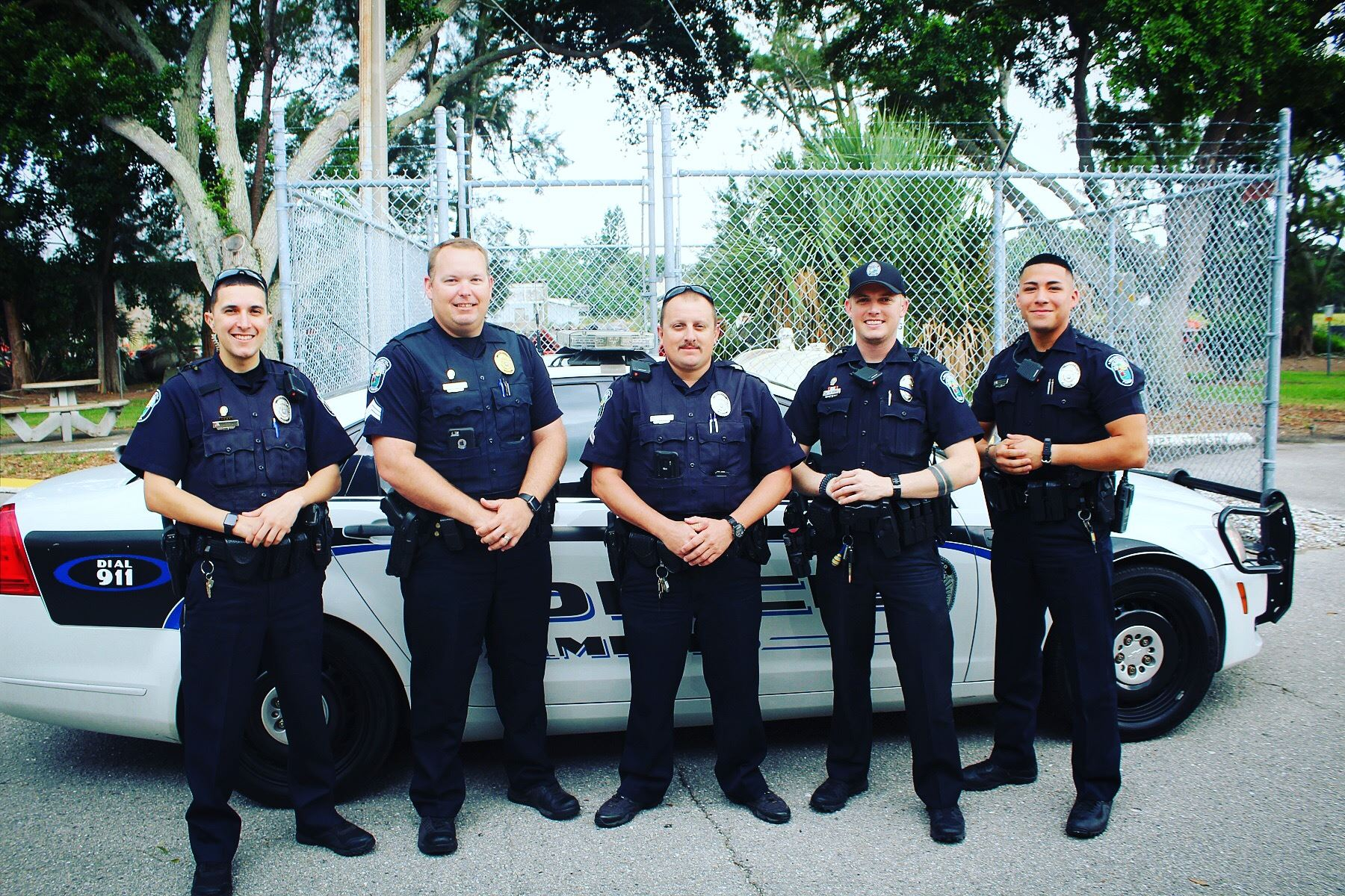 squad of five uniformed ppd officers standing in front of a marked police car