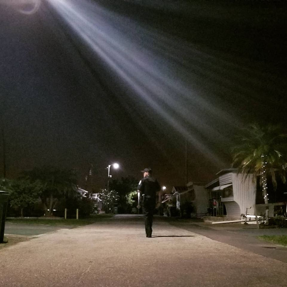 officer walking down a neighborhood street at night on foot patrol