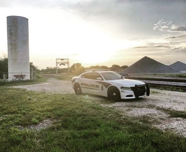 patrol car in a deserted construction site near railroad tracks with sunset in the background